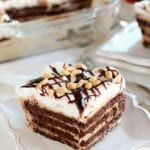 Piece of peanut butter fudge icebox cake on a white square plate sitting on a white table next to a clear glass baking dish of the rest of the cake
