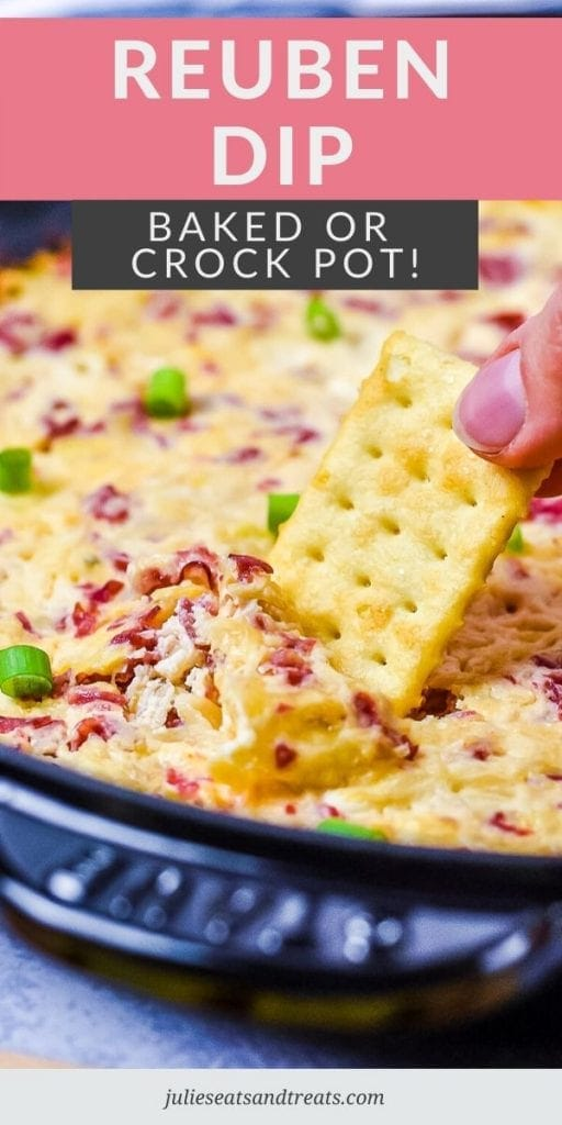 Hand dipping a cracker into Reuben Dip