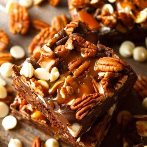 Stack of turtle brownies on a table with pecans and white chocolate chips
