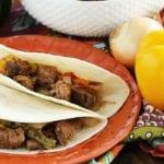 Two crock pot steak fajitas on an orange plate next to a yellow bell pepper, an onion, and a white bowl of steak fajita filling