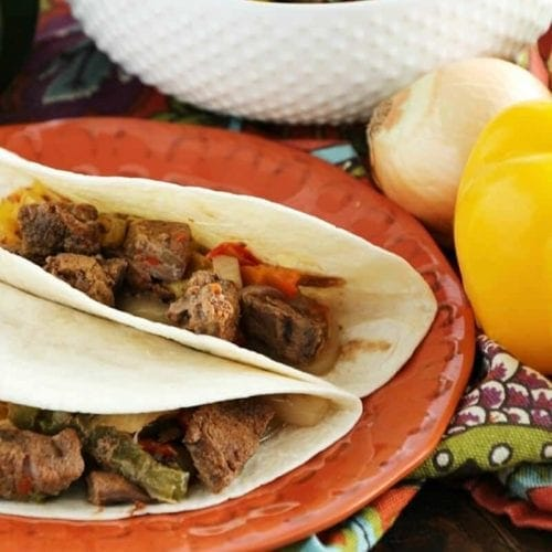 Two crock pot steak fajitas on an orange plate next to a yellow bell pepper, an onion, and a white bowl of steak fajita filling