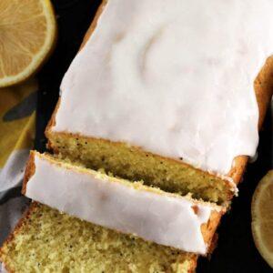 Partially sliced loaf of glazed lemon poppy seed bread next to sliced lemons