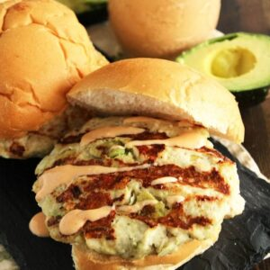 A chicken avocado burger on a bun with chipotle yogurt sauce on a slate tray next to a glass jar of chipotle yogurt sauce and an avocado sliced in half