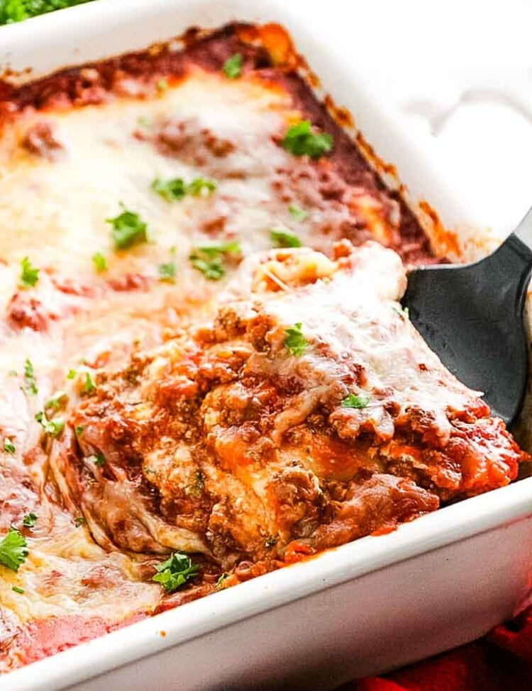 Lasagna being scooped out of baking dish with spatula