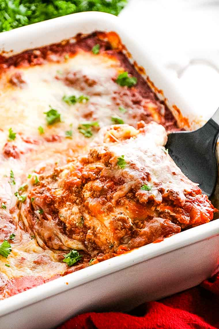 A spatula scooping a piece of lasagna out of baking dish