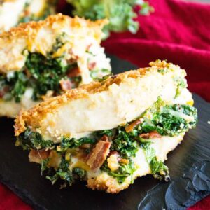Three cheesy bacon kale stuffed chicken breasts on a slate tray sitting on a red kitchen towel