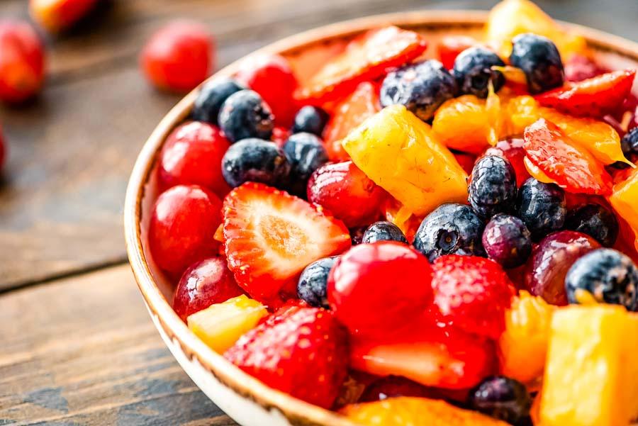 Bowl of fruit salad on wood background