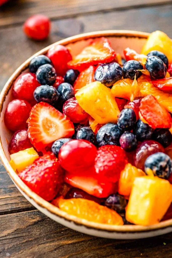 fruit salad of strawberries, blueberries, red grapes, pineapple and orange in a white bowl