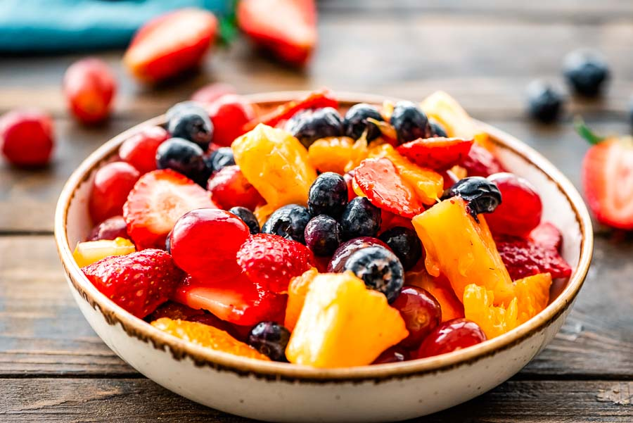 glazed fruit salad in serving bowl with blueberries, strawberries, grapes, pineapples