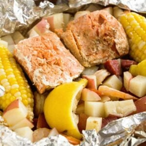 A foil packet of cajun shrimp boil including potatoes, corn on the cob, fish, and lemons