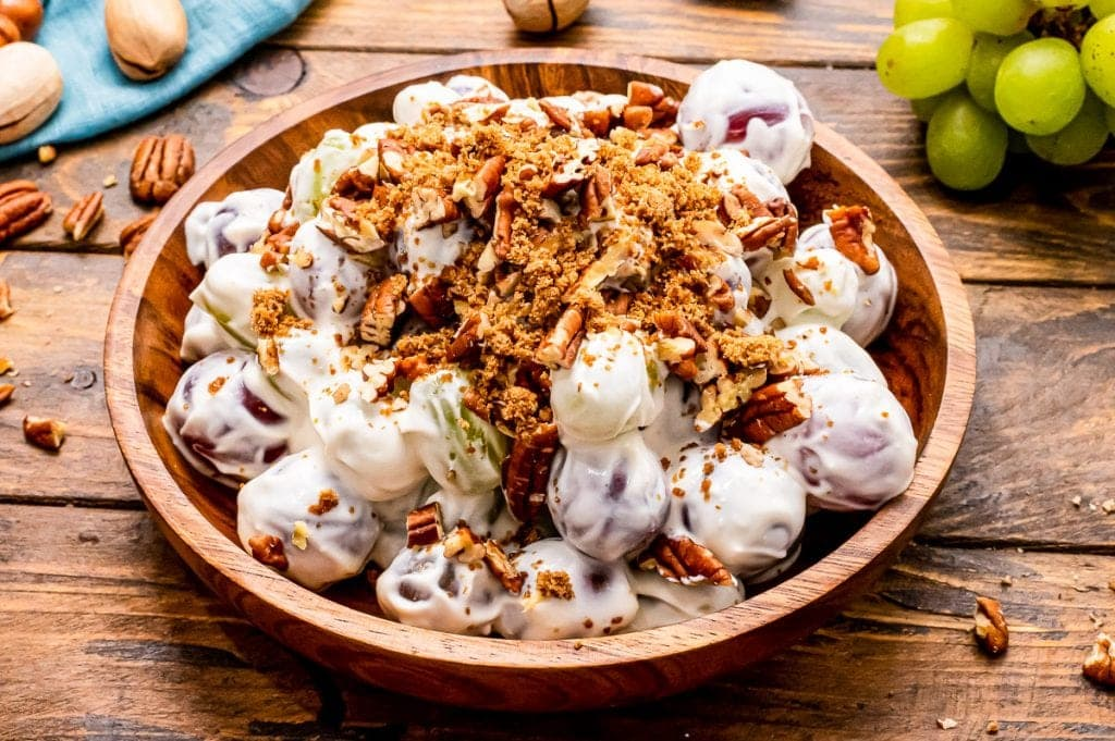 Bowl bowl with prepare grape salad in it with brown sugar and chopped pecans sprinkled on top.