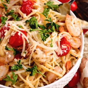 A white bowl of garlic shrimp tomato pasta topped with parsley and shredded Parmesan