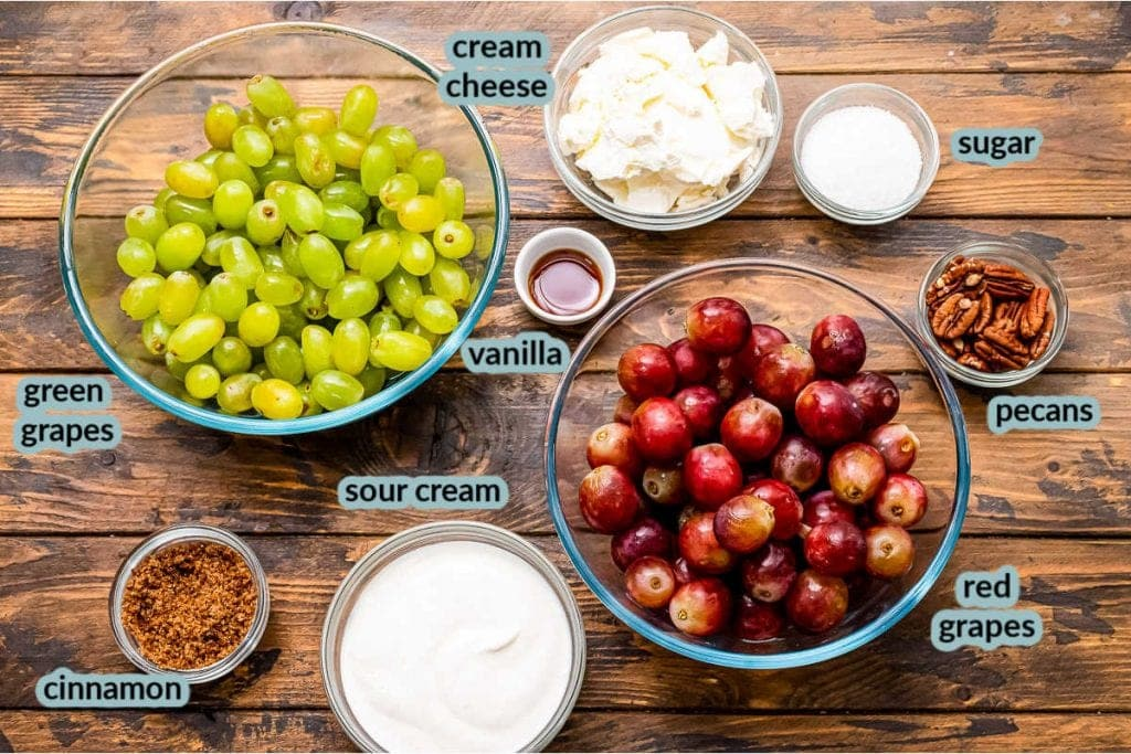 Ingredients in glass bowls on wood background for grape salad. Bowls of red grapes, green grapes, cream cheese, sour cream, brown sugar, pecans, vanilla etc.