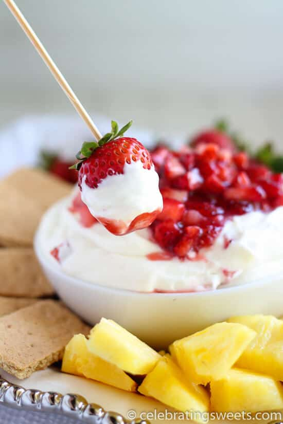Strawberry on wooden skewer with fruit dip on it a bowl of fruit dip in background with dippers