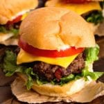 Three whiskey cheddar burgers on parchment paper sitting on a wood table