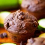 Double chocolate zucchini muffins on a wood table with chocolate chips and zucchini slices