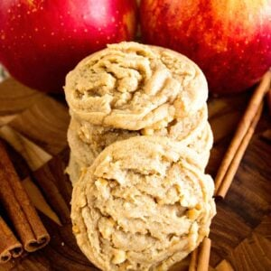 Two stacks of apple peanut butter cookies on a wood board with cinnamon sticks and apples