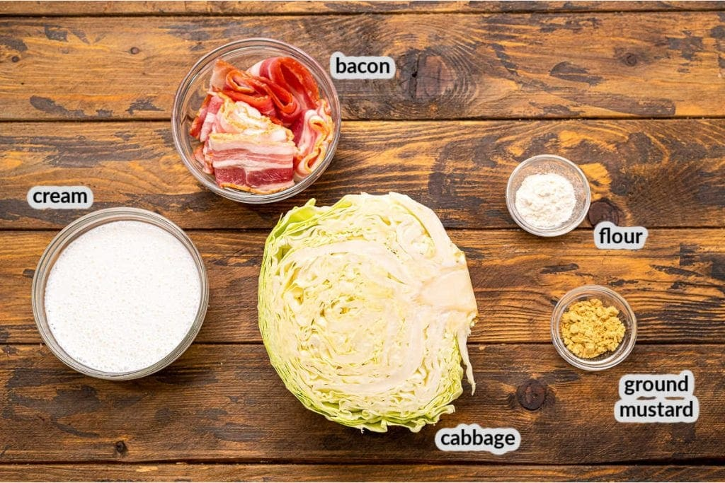 Overhead image of ingredients for cabbage casserole including half head of cabbage, bacon strips, cream, flour and ground mustard in bowls.