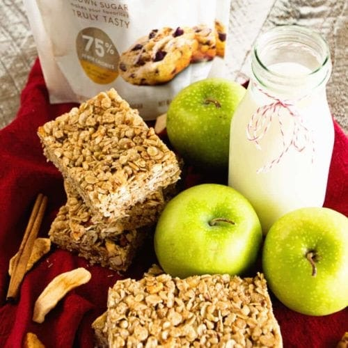 Two stacks of chewy apple cinnamon granola bars on a red kitchen towel with three green apples, a glass of milk, cinnamon sticks, dried apple slices, and a bag of truvia brown sugar