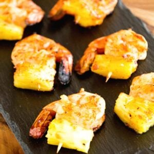 Two rows of grilled bbq pineapple shrimp bites on a slate tray