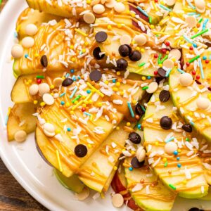 Apple Nachos topped with peanut butter, chocolate chips, coconut and sprinkles. on white plate