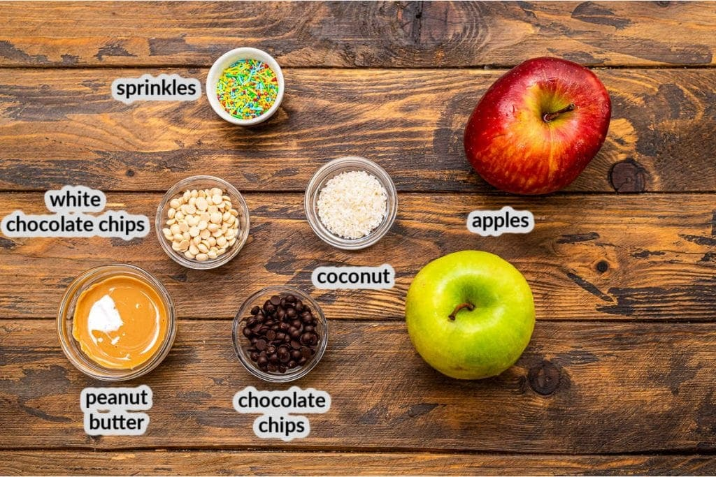 Overhead image of apple nachos ingredients including apples, peanut butter, chocolate chips, coconut and sprinkles in glass bowls.