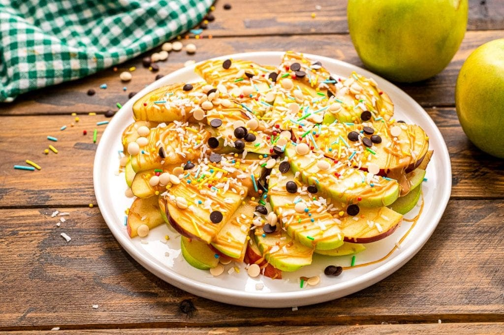 White plate with thinly sliced apples drizzled with peanut butter, chocolate chips, sprinkles and coconut.