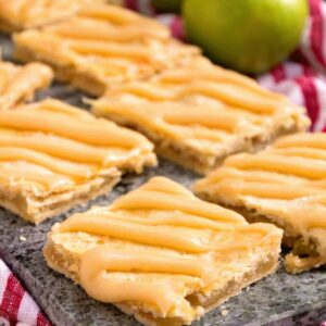 Eight apple pie bars on a stone tray sitting on a white and red kitchen towel along with two green apples