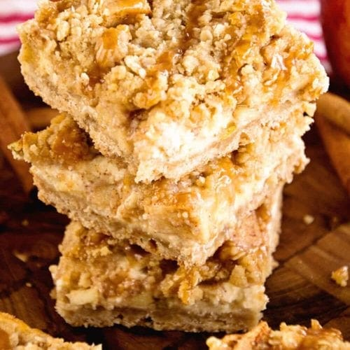 A stack of three caramel apple cheesecake bars on a wood board next to more bars and some apples
