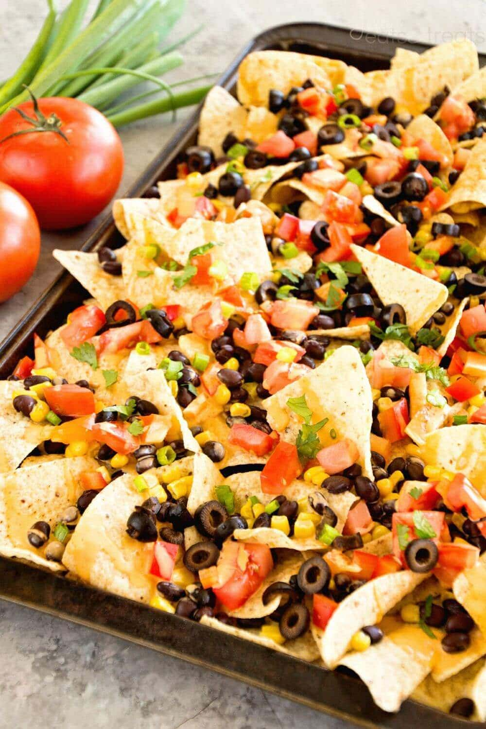 Southwestern Nachos with Chipotle Sauce ~ Tortilla Chips Loaded with Corn, Black Beans, Red Pepper, Tomatoes, Black Olives, Cilantro and Green Olives! Topped off with a spicy Chipotle Sauce! The perfect Vegetarian Appetizer!