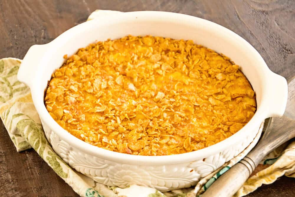Step by step directions how to make corn pudding recipe ~ served in a white casserole dish topped with a crunchy corn flake topping!