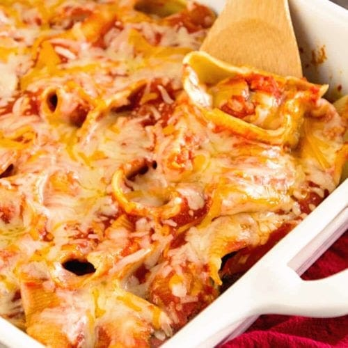 Easy meatball stuffed shells in a white baking dish with a wood spoon
