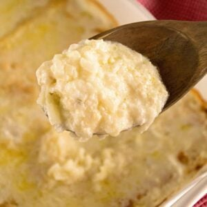 A wooden spoon with a scoop of hashbrown potatoes on it being held over a white casserole dish of hashbrown potatoes