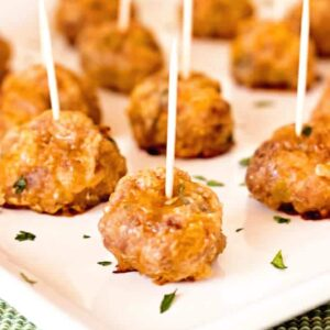 Mexican sausage balls with toothpicks in each one on a white plate