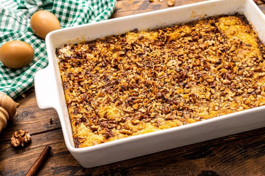 Pumpkin Dump Cake in white rectangle baking dish with green and white checkered napkin behind it.