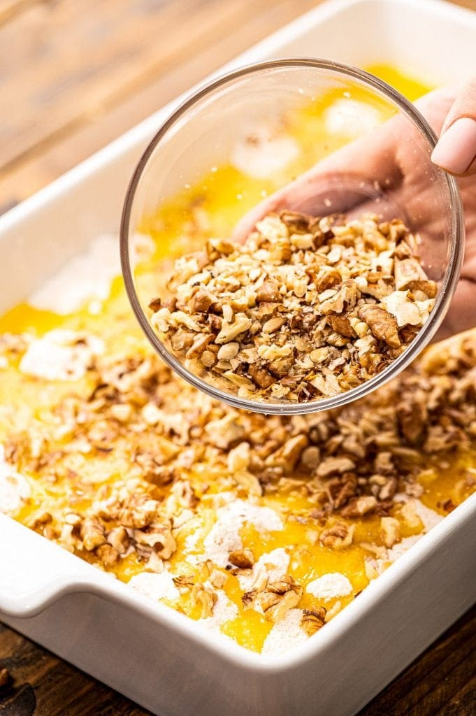Hand pouring chopped walnuts on top of cake before baking