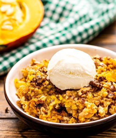 Pumpkin Dump Cake in a bowl with a scoop of ice cream on top. A green and white checkered napkin behind it.