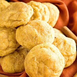 A pile of pumpkin snickerdoodle cookies on an orange cloth napkin with cinnamon sticks