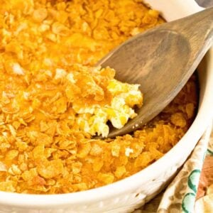 A white bowl of corn pudding casserole with a wooden spoon