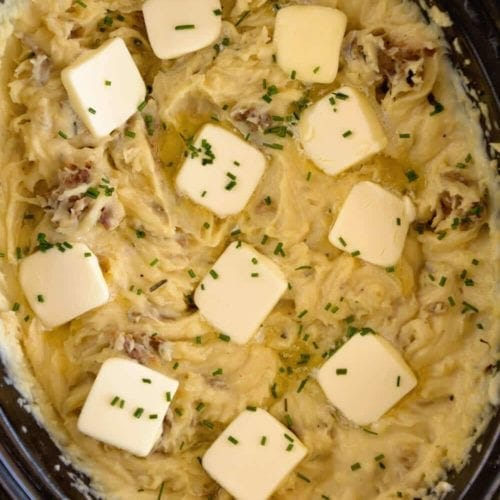 Overhead image of a black crock pot full of garlic mashed potatoes topped with several pads of butter