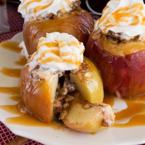 Three light crock pot baked apples with whipped cream and caramel sauce on a white plate sitting on a red kitchen towel with cinnamon sticks