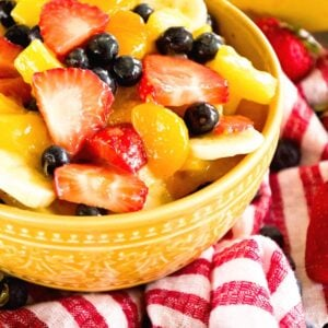 A yellow bowl of sunshine fruit salad on a red and white striped kitchen towel along with strawberries, blueberries, and bananas