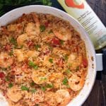 Overhead image of light Italian shrimp and rice in a skillet on a wood table next to fresh parsley and a bottle of Thrive oil