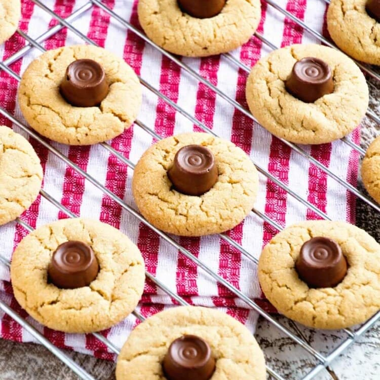 Overhead image of rolo peanut butter blossom cookies on a cooling rack over a red and white striped towel