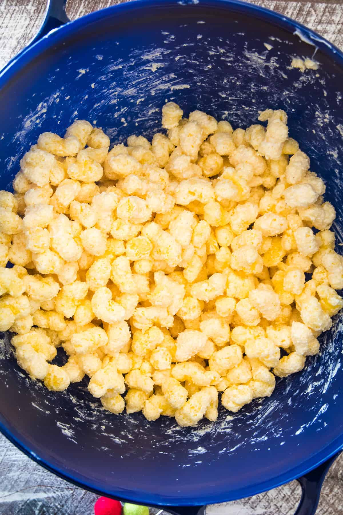 Blue bowl with puffcorn being mixed with white chocolate chips