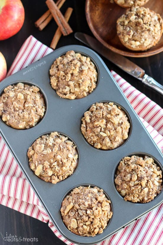 Overhead image of a tin of 6 muffins with streusel topping on red striped napkin.