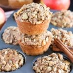 A six muffin tin of apple oat muffins with two more muffins stacked on top