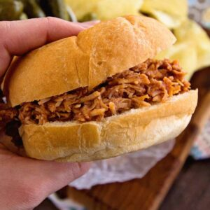 Hand holding a crock pot smokey bbq chicken sandwich over a board with pickles and potato chips on it
