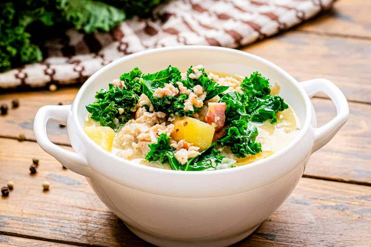 White bowl with slow cooker zuppa toscana in it