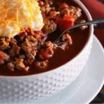 A white bowl of light crock pot spicy turkey chili with a spoon and topped with sour cream and shredded cheese